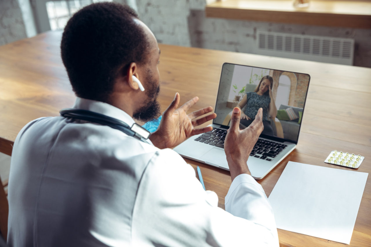 Person a lady online with laptop. African-american doctor during his work with patients, explaining recipes for drug. Daily hard work for health and lives saving during epidemic.