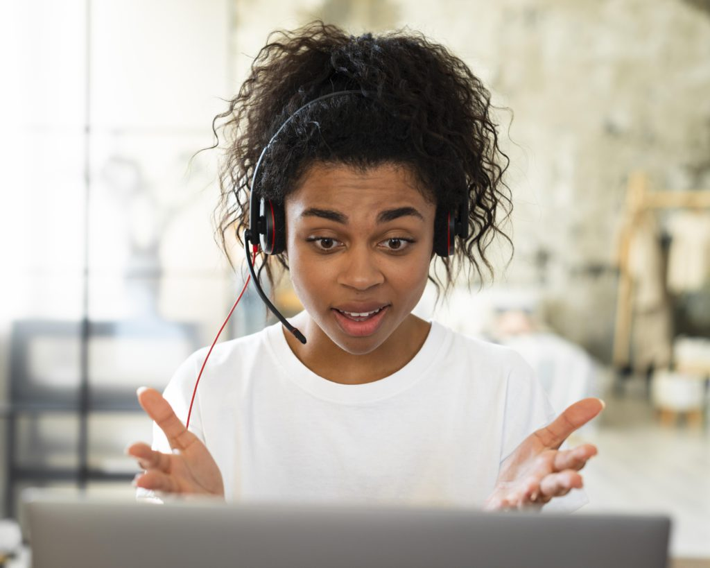 A woman reacts during a video meeting.