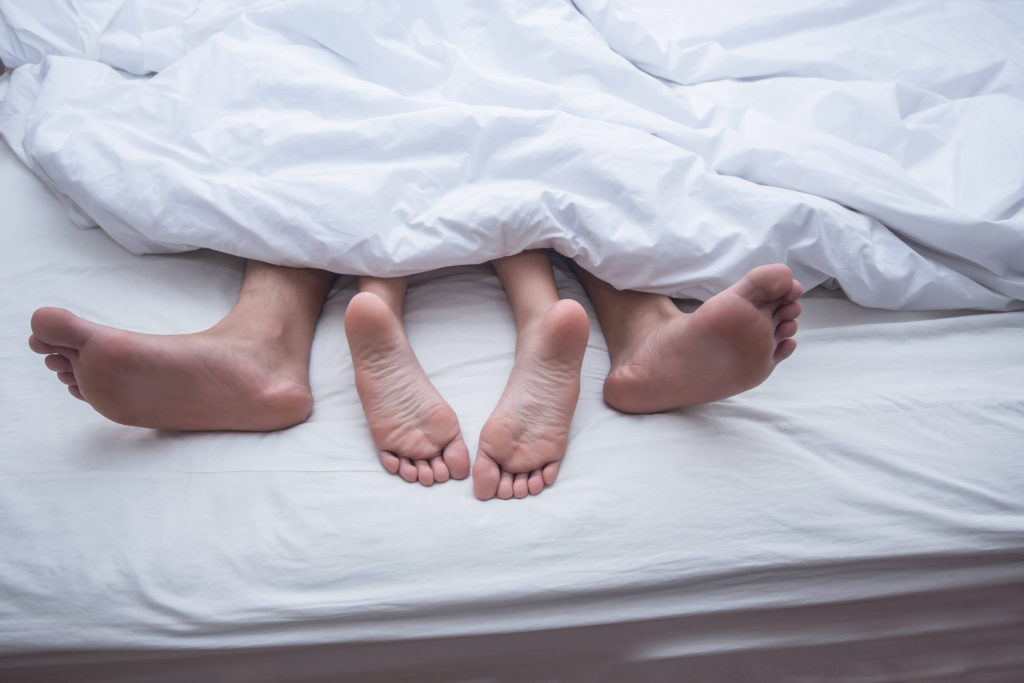 Close up legs of couple in bed.